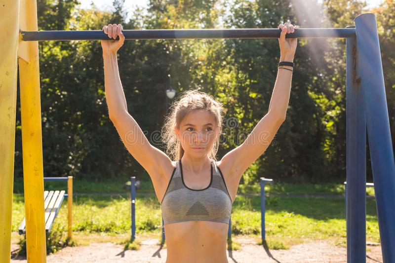 Young beautiful girl doing chin-ups on the outdoor sports ground.  royalty free stock photo