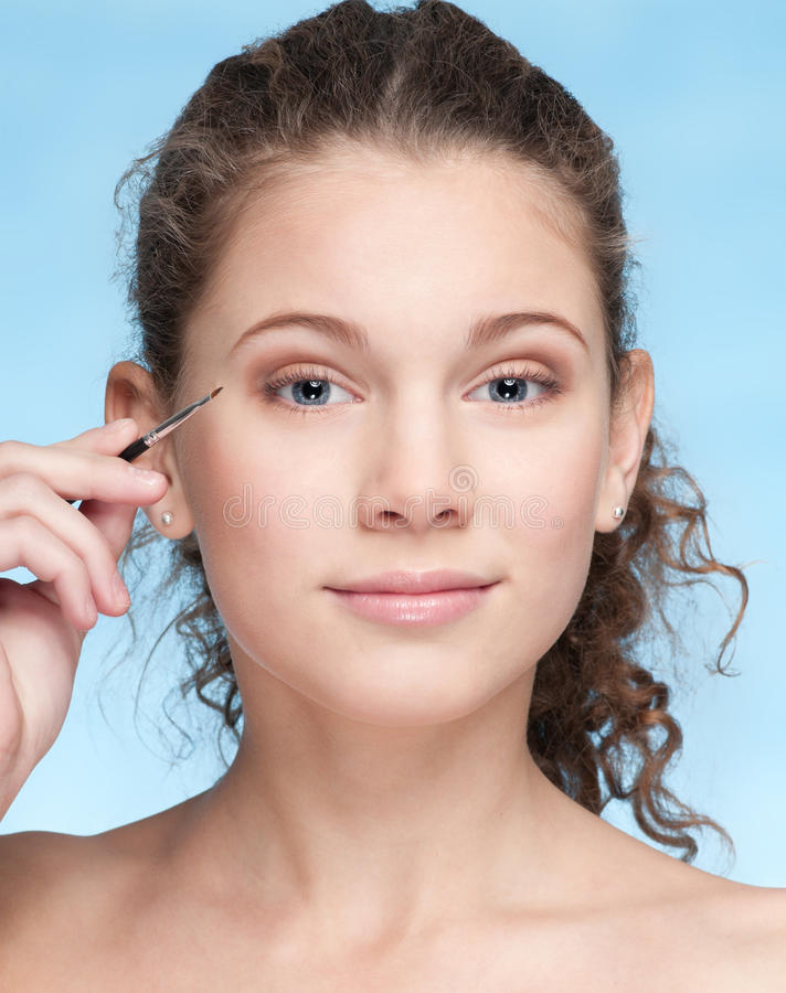 Young beautiful girl doing make-up by brush stock photo