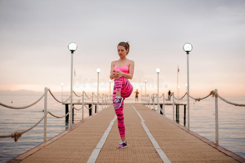 Young and beautiful girl doing morning exercises on the wooden bridge stock images