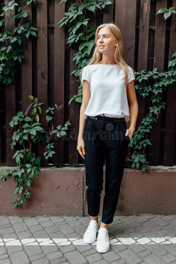 a beautiful girl dressed in a white t-shirt stands outdoors, against a wooden deciduous wall stock photo