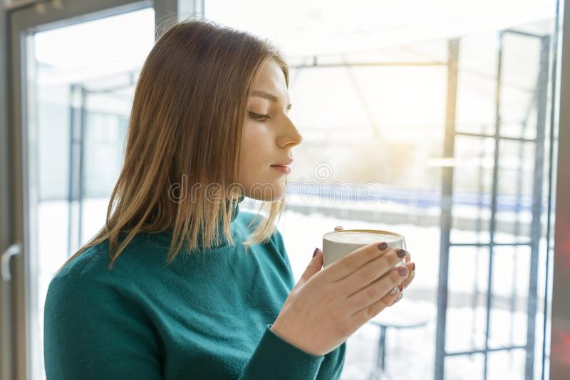 Young beautiful girl drinking coffee, standing in profile, looking out the window. Autumn winter season in coffee shop.  stock photography