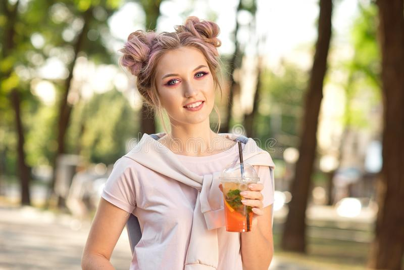 Young beautiful girl drinking fresh juice from plastic takeaway food cups after a walk outdoors. Healthy lifestyle royalty free stock photo