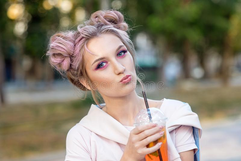 Young beautiful girl drinking fresh juice from plastic takeaway food cups after a walk outdoors. Healthy lifestyle stock photography