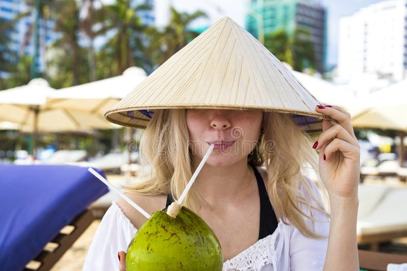 Young beautiful girl drinks from a coconut stock photography