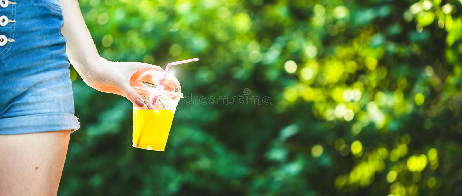 Young beautiful girl drinks freshly squeezed juice on a background of juicy foliage Banner concept royalty free stock photography