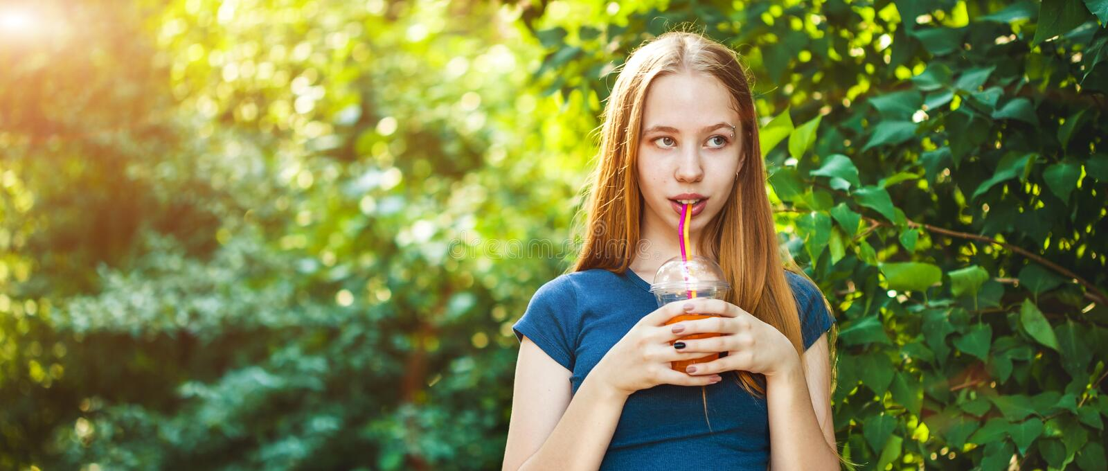 Young beautiful girl drinks freshly squeezed juice on a background of juicy foliage Banner concept stock image