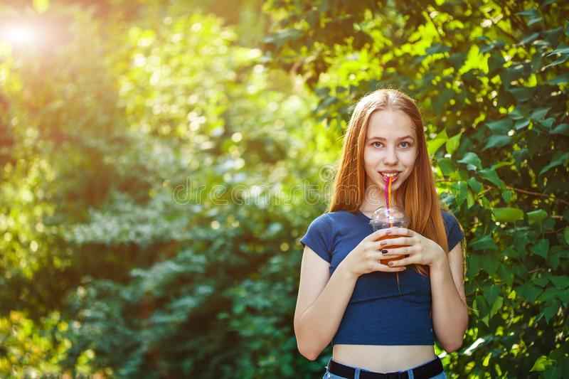 Young beautiful girl drinks freshly squeezed juice on a background of juicy foliage royalty free stock images