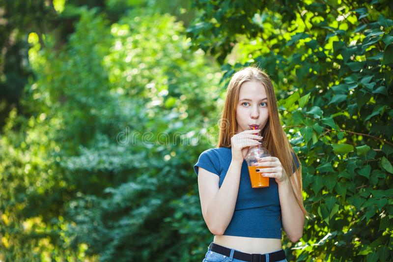 Young beautiful girl drinks freshly squeezed juice on a background of juicy foliage Copy space stock photography