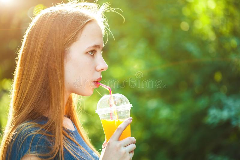 Young beautiful girl drinks freshly squeezed juice on a background of juicy foliage Copy space stock photos