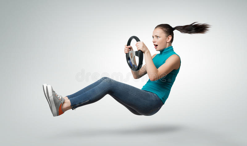 Young beautiful girl driver with a wheel, auto concept. On background royalty free stock photo