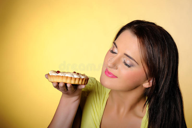 Young beautiful girl eating small sweet cake stock photo