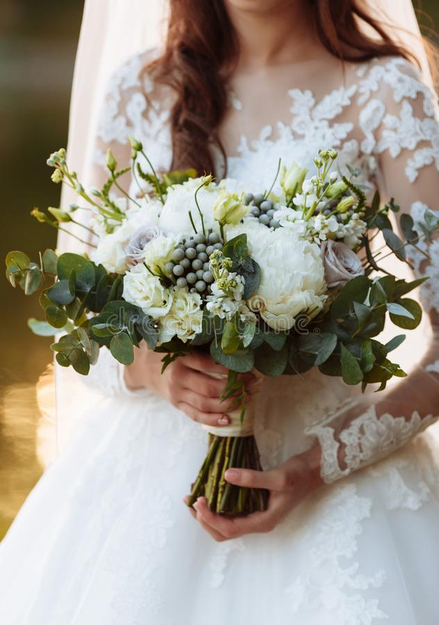 Young girl in an elegant dress is standing and holding hand bouquet of pastel flowers and greens with ribbon at nature royalty free stock images