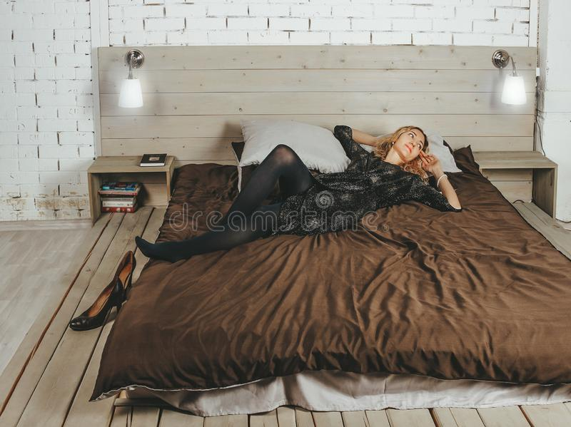 Young beautiful girl in an evening dress close-up lying on the bed after a party on the background of white brick wall royalty free stock photo