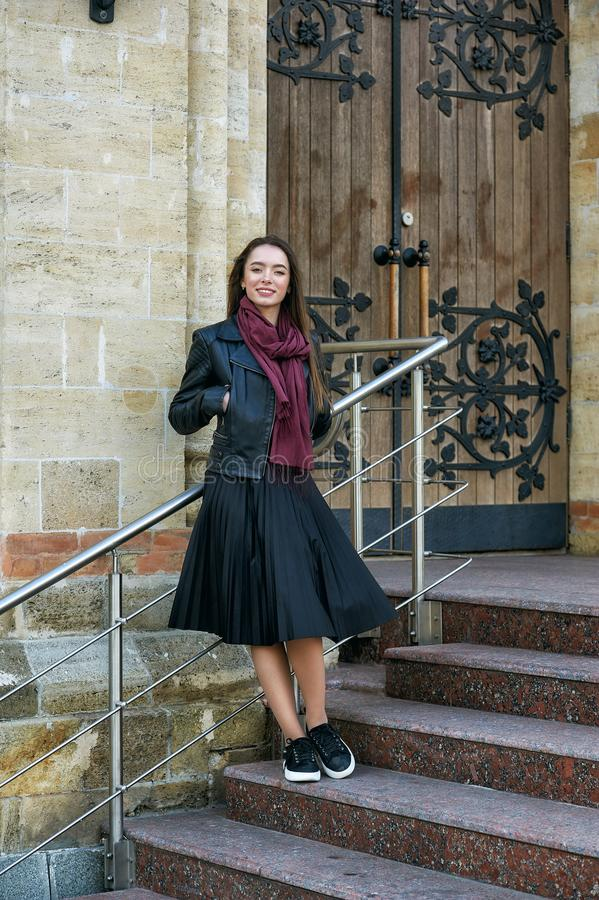 Young beautiful woman on a walk around the city . The girl wears a black jacket and skirt . stock images