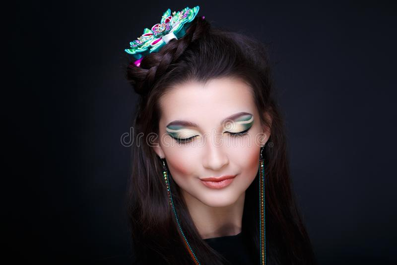 Woman long earrings. Young beautiful girl, fashionable tied hairdo, professional makeup. Bright glitter eye shadows, perfect shape of brows, shiny glossy lips stock images