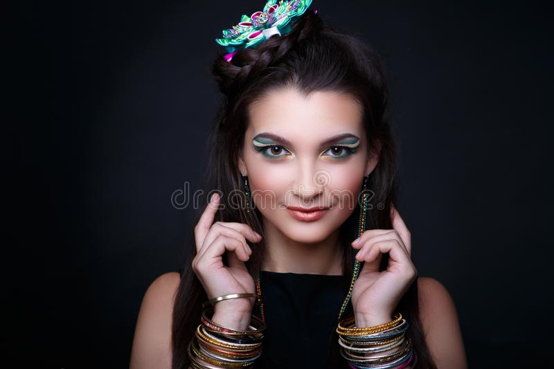 Many Hand bracelets. Young beautiful girl, fashionable tied hairdo, professional makeup. Bright glitter eye shadows, perfect shape of brows, shiny glossy lips stock photography