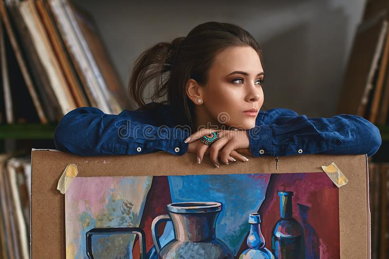 Young beautiful girl, female artist painter thinking of a new artwork idea or project holding a finished picture artwork stock photos