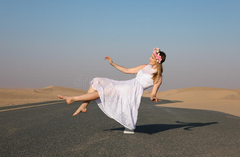 Young beautiful girl floating in the air. Young beautiful girl woth blonde hair nd flower crown floating in the air in the desert royalty free stock photo