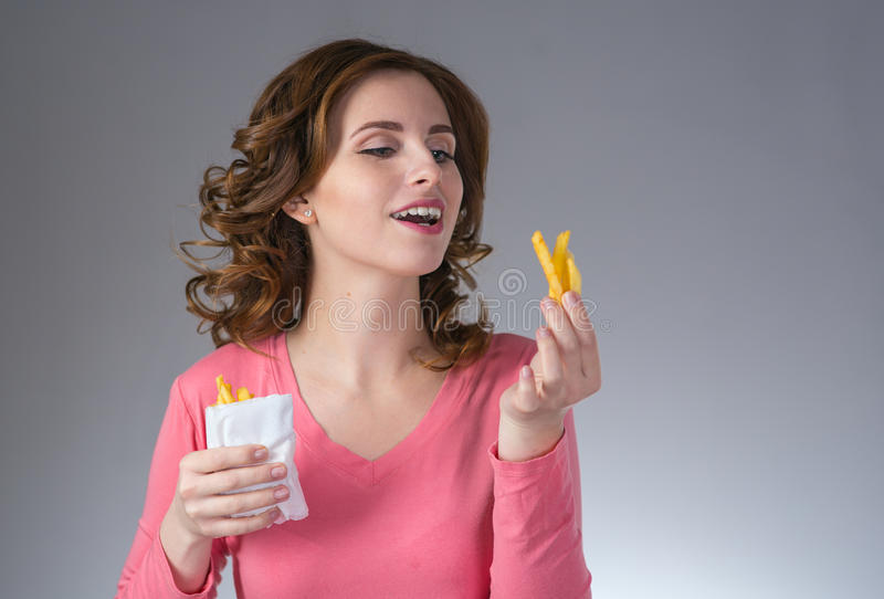 young beautiful girl with a French fries from a fast food smiling royalty free stock photography