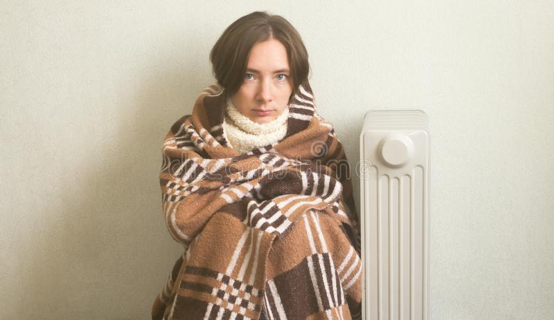 Young beautiful girl froze and warms hands near a radiator, dressed in warm woolen plaid. Young beautiful girl froze and warms hands near a radiator, dressed in stock images