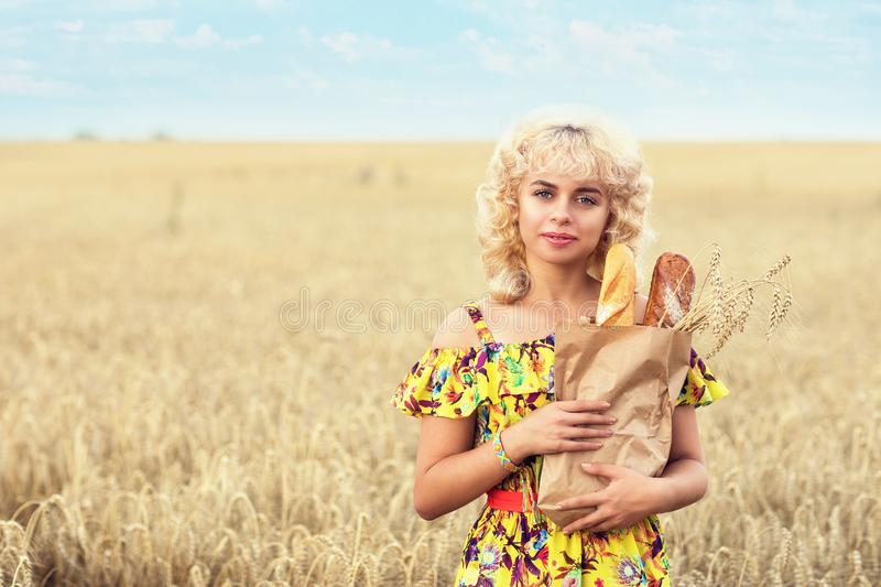 Young beautiful girl with a full pack of bread in a field with ripe wheat. Model posing against a background of crops. Copy space royalty free stock image