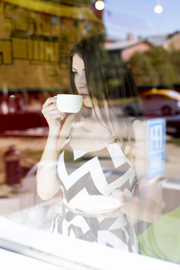 Young beautiful girl in glass showcase a cafe, sunny day, holding mug of tea. Young beautiful girl in a glass showcase in a cafe, sunny day, holding a mug of tea royalty free stock photo