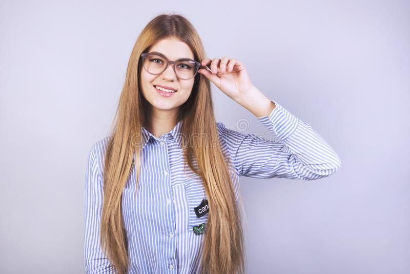 Young beautiful girl with glasses standing in front of grey background and smiling and wearing a shirt, a lot of clean stock photography