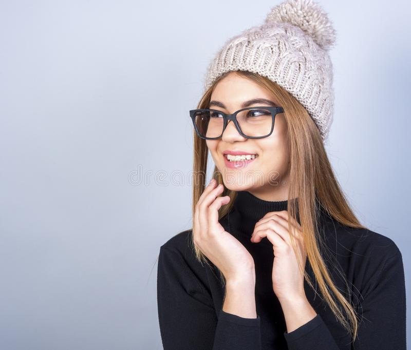 Young beautiful girl with glasses and winter hat standing in front of grey background, a lot of clean space stock photos