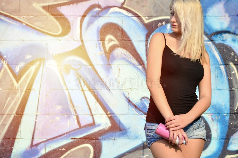 A young and beautiful girl graffiti artist with a paint spray stands on the wall background with a graffiti pattern royalty free stock photos