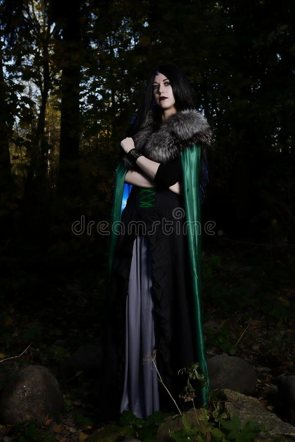 Young beautiful girl in green raincoat, looks as witch on Halloween in dark forest royalty free stock photo
