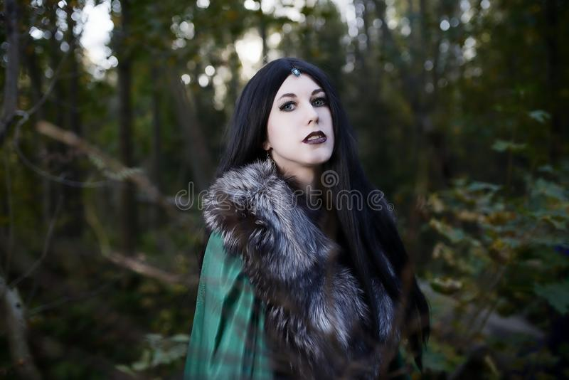 Young beautiful girl in green raincoat, looks as witch on Halloween in forest royalty free stock images