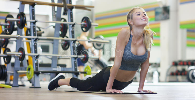 A young beautiful girl in a gym, leaning on her hands, shakes the press, making long steps, bending her knees. Concept: to love sp. Orts, to attend a gym, proper royalty free stock photography