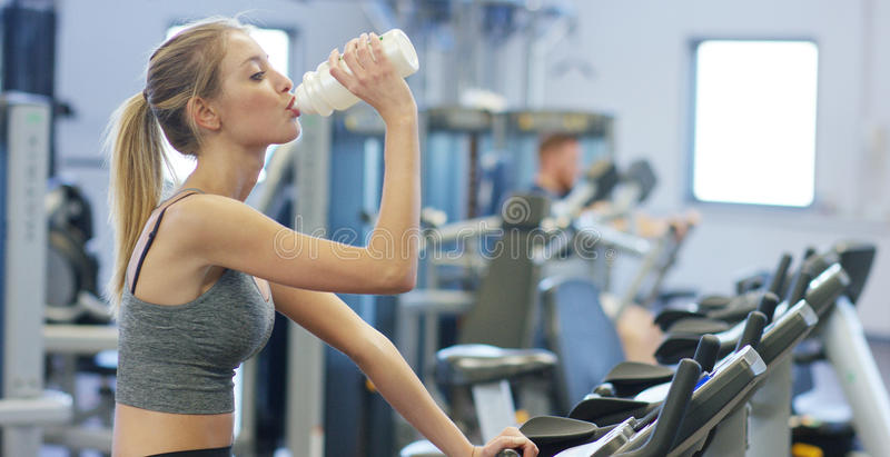 Young beautiful girl in gym, shaking her legs on cycling simulator, smiling at camera. The concept: to love sports, to attend a gy royalty free stock image