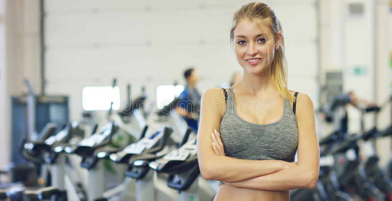 Young beautiful girl in the gym, stands smiling with a towel on her shoulder after the coaching and relaxed. Concept: to love spor stock photo
