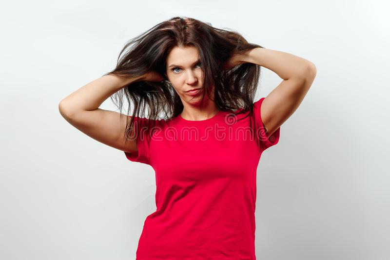 Young, beautiful girl has a disheveled hair, a bad day for hair, isolated on a light background. Different human emotions,. Feelings of facial expression royalty free stock image