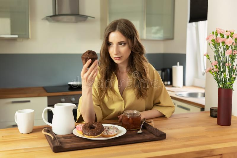 Young beautiful girl having breakfast at home in the kitchen. royalty free stock photos