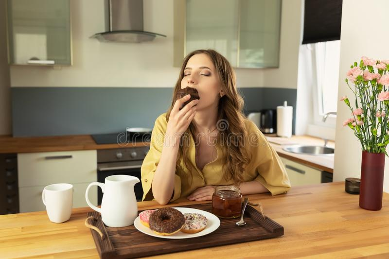 Young beautiful girl having breakfast at home in the kitchen. royalty free stock images