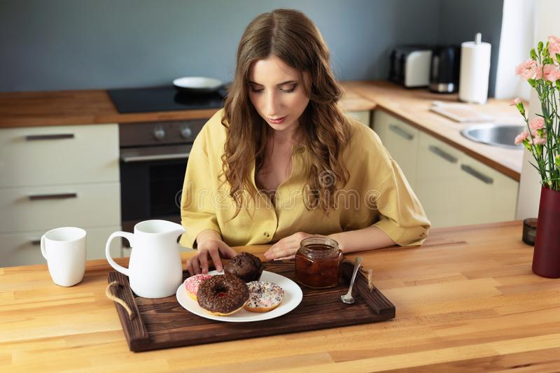 Young beautiful girl having breakfast at home in the kitchen. stock photography