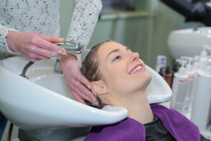 Young beautiful girl having hairwash in salon closeup stock images