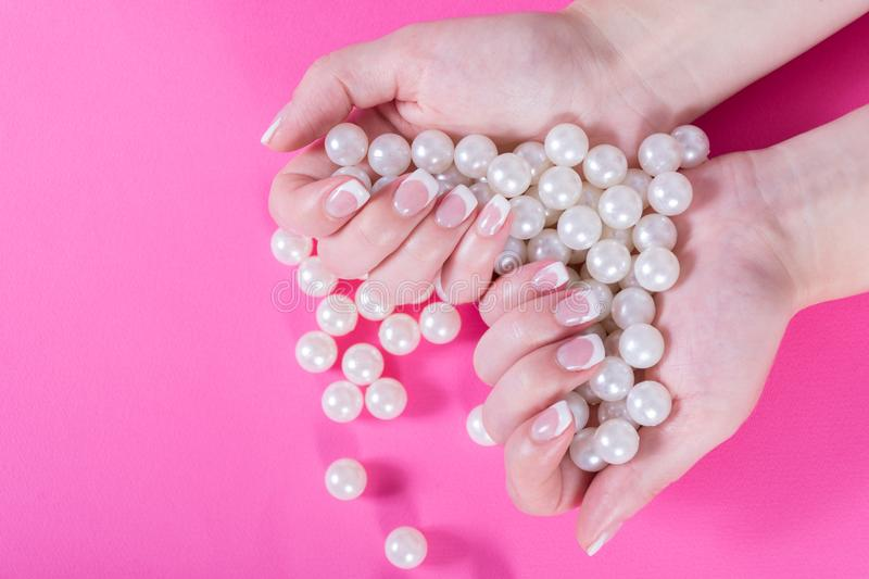 Young female holding many pearls in hand with french nails polish isolated on pink. Young beautiful girl holding many pearls in hand with french nails polish royalty free stock image