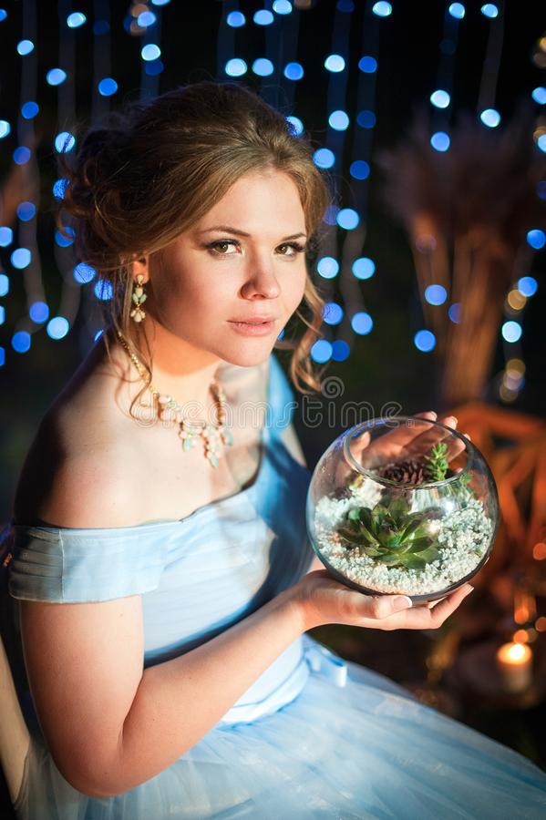 Young beautiful girl holding a vase with succulent plants on a dark background with lights royalty free stock image