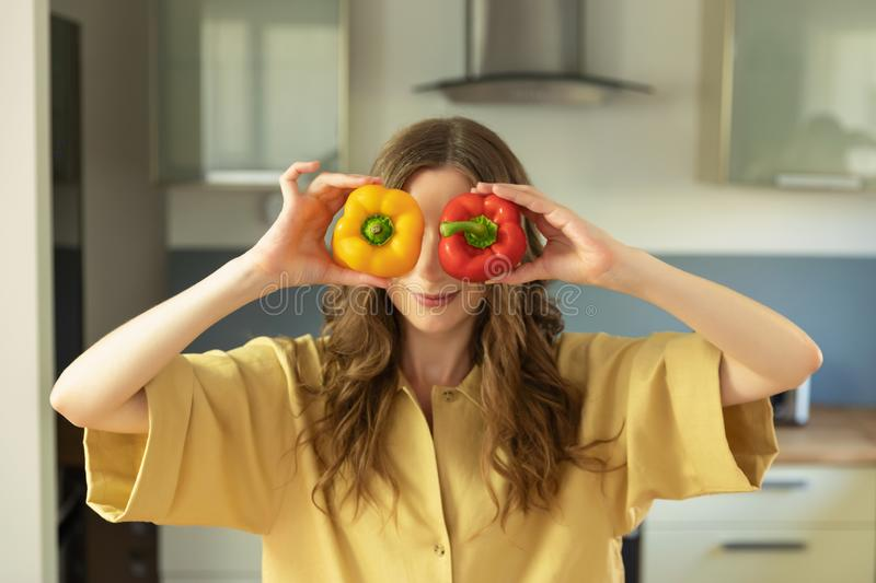 A young beautiful girl holds a sweet pepper in her hands, have fun and closes their eyes. royalty free stock image