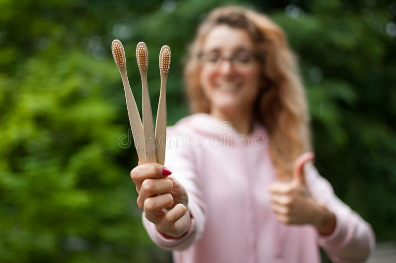 Young beautiful girl holds a useful three bamboo toothbrushes and shows thumb. Environmental friendliness and zero waste.  stock photography