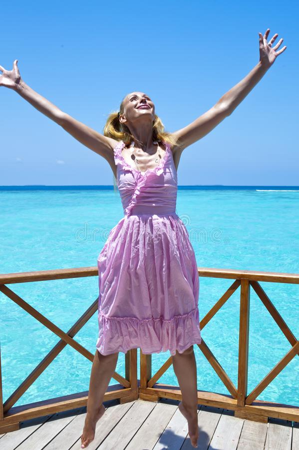 Young beautiful girl jumps in pink sundress on platform of villa on water, Maldives royalty free stock photos