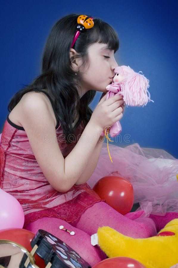 Young and beautiful girl kissing her doll. Surrounded by balloons and make up kit stock photos