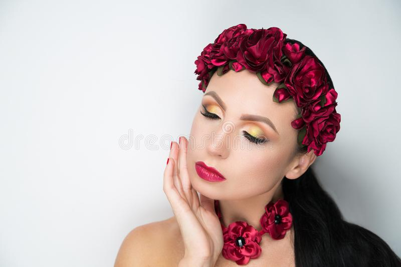 Woman flower wreath. Young beautiful girl lady model with a fashionable flower tiara. professional make-up arrows eye shadows long lashes, stylish matte vine royalty free stock images