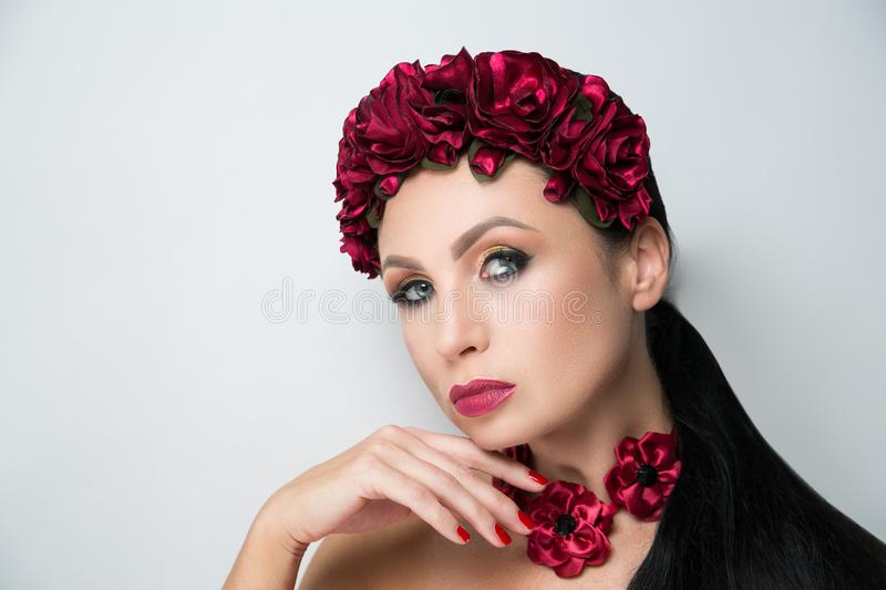 Woman flower wreath. Young beautiful girl lady model with a fashionable flower tiara. professional make-up arrows eye shadows long lashes, stylish matte vine stock image