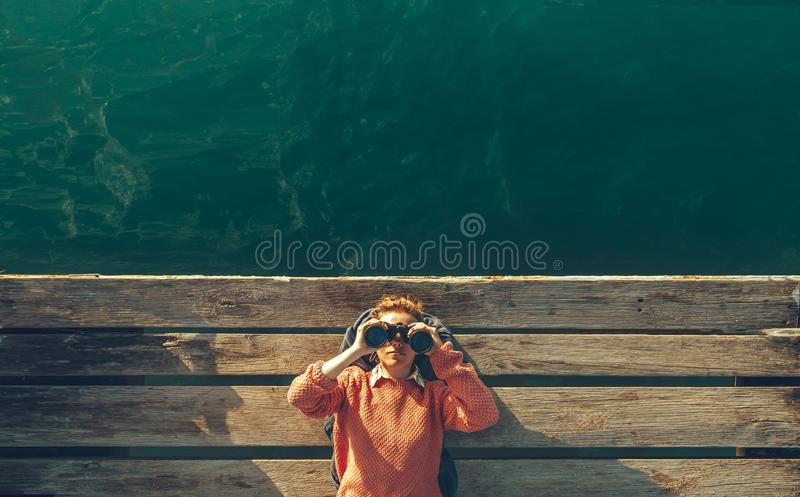 Young Beautiful Girl Lies On A Pier Near The Sea And Looks Through Binoculars On The Sky. Travel Search Journey Concept stock photography