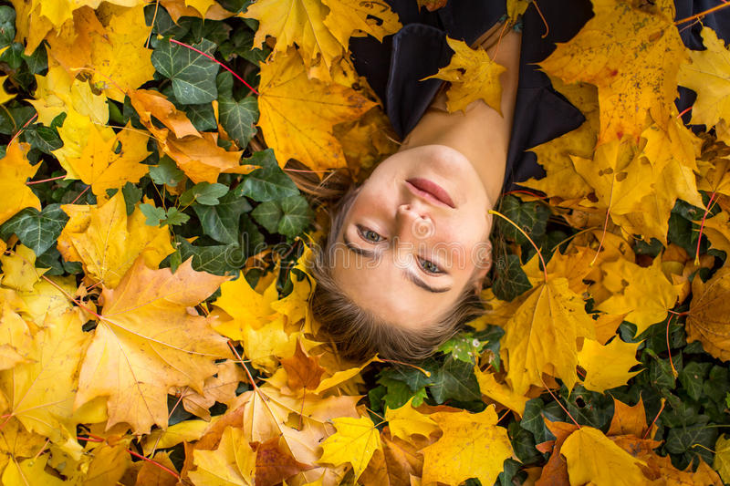 Young beautiful girl lies on a yellow autumn fallen leaves. stock photo