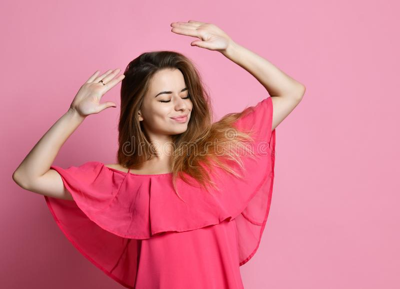 girl dancing against wall with smile, rejoicing good mood. Student female having fun while dancing to some pleasant music indoors stock images